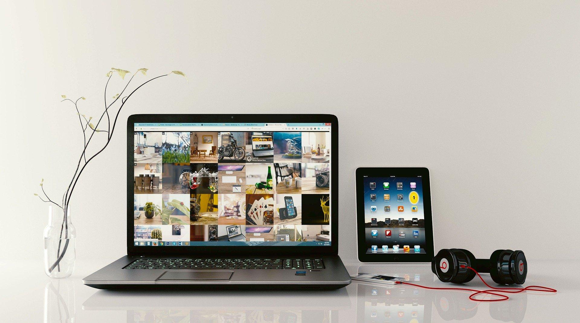 laptop uzyskany poprzez wypożyczenie laptopa leży na stole razem z tabletem, słuchawkami i wazonem