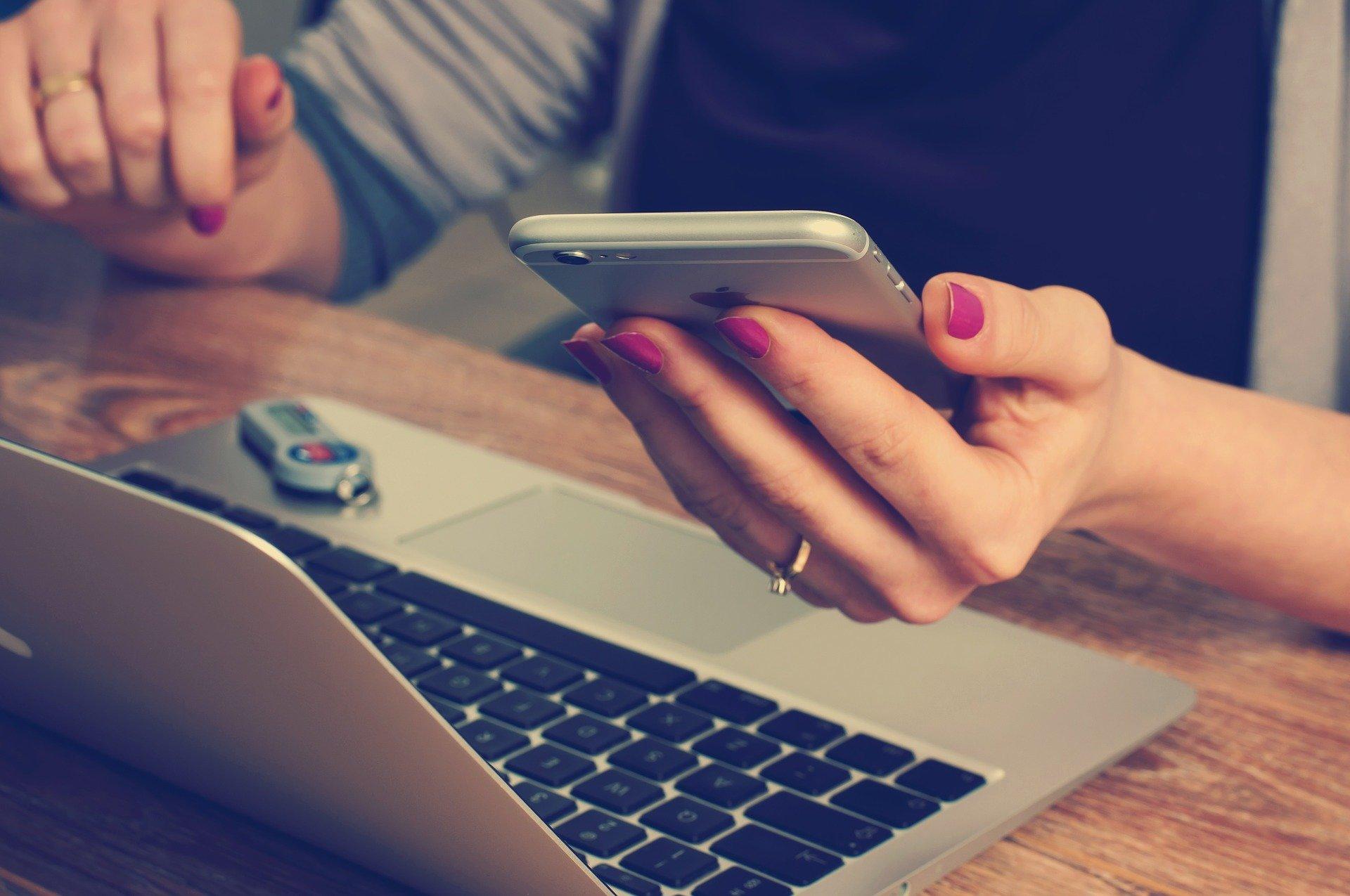 Laptop z wynajmu laptopów biznesowych jest używany przez kobietę, która w ręku trzyma telefon.