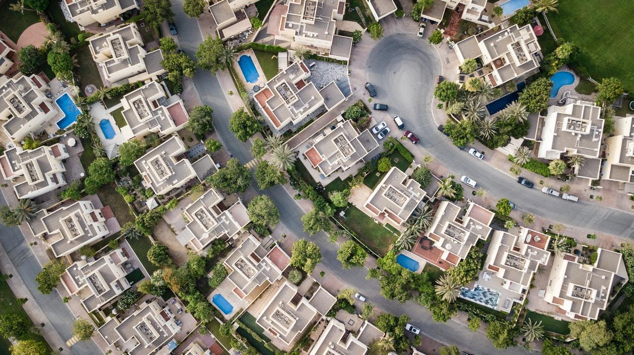 Nieruchomości z gdańskiego skupu nieruchomości za gotówkę. Widać bogatą dzielnicę z lotu ptaka. Baseny, samochody itd.